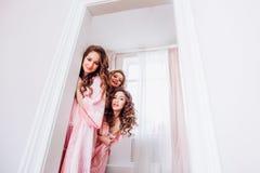 r 桃红色睡衣的三个女孩偷看从后面一个白色门和邀请到党 免版税库存图片