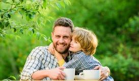 r 父亲和男孩户外饮料茶 开发健康饮食习惯 饲料婴孩 自然营养概念 免版税图库摄影