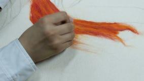 r 白色衬衫的一个少年戳在橙色干燥毛毡的一根针 做图片色的羊毛在a 影视素材
