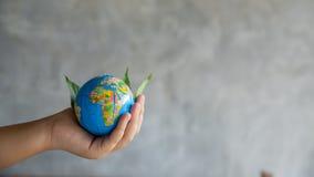 r 绿色行星在您的手上 库存照片