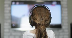 r 耳机的女孩看聪明的电视 影视素材