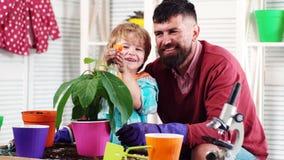 r 逗人喜爱的儿童男孩帮助他的爸爸喜欢植物 E 有男孩植物的人 股票录像