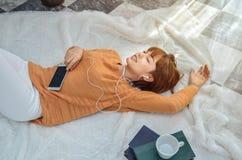 穿橙色衬衣的妇女听到音乐并且是愉快的 免版税图库摄影