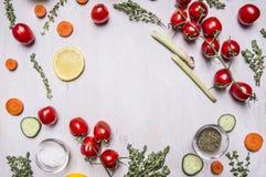 在一个分支的西红柿用晒干盐的切的黄瓜柠檬红萝卜各种各样的草本排行了文本的框架地方木r的 免版税图库摄影