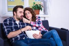 年轻在电视和吃玉米花的夫妇观看的电影在居住的r 库存图片