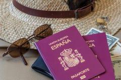 r Chapeau, lunettes de soleil, argent et passeports femelles Photographie stock libre de droits