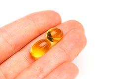 R?cka den h?llande kapseln av omega 3 p? vit bakgrund close upp royaltyfria foton