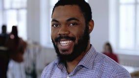 r Close-upportret die van het jonge zwarte managerzakenman knipogen, op modern in kantoor stellen stock video