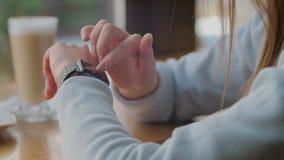 r closeup Mulher de negócios que usa a aplicação móvel dos relógios espertos na moda no tela táctil filme