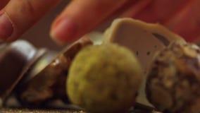 R?cznie robiony czekoladowi cukierki spada na drewnianym tle, smakowici cukierki w zwolnionego tempa uhd zdjęcie wideo