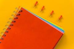R?d anteckningsbok p? gul pastellf?rgad rosa bakgrund arkivbild