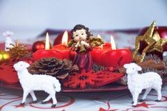 R?d jul dekorerade kransplattan med fyra brinnande stearinljus p? en tabelltorkduk som omgavs med vita f?r arkivbild