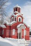 R?d kristen kyrka i vintern, sn? p? taket royaltyfria bilder