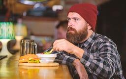 r De brutale hipster gebaarde mens zit bij barteller Bedrieg maaltijd Hoog Calorievoedsel heerlijk stock afbeeldingen