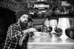 r r De brutale hipster gebaarde mens zit bij barteller Bedrieg maaltijd stock afbeelding