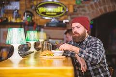 r r De brutale hipster gebaarde mens zit bij barteller Bedrieg maaltijd royalty-vrije stock afbeeldingen
