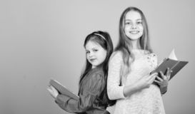 r De nuevo a escuela Hermandad de la amistad peque?as muchachas con los cuadernos Estudiantes que leen un libro imágenes de archivo libres de regalías