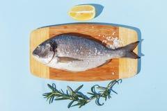 R? doradofisk p? ett tr?br?de, ingredienser f?r att laga mat och kryddor p? en bl? bakgrund royaltyfri bild