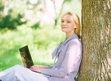 r   E Работа девушки с ноутбуком в парке сидеть стоковая фотография