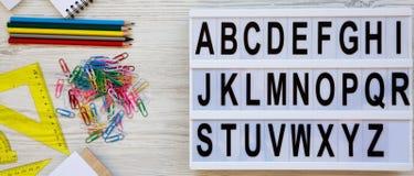 r E 在现代委员会和辅助部件的英语字母表在白色木表面的研究的 免版税库存照片