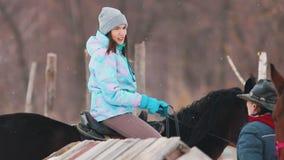 r Een jonge vrouw die een paard in een dorp berijden stock footage