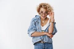r?ellement Le portrait d'amus? et de amuser a interrog? la jeune femme 20s attirante en verres et denim regardant de dessous images libres de droits
