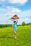 6 år gammal pojkespring med draken Royaltyfri Fotografi