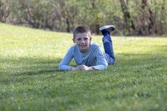 7 ?r gammalt barn som ligger p? gr?set i, parkerar fotografering för bildbyråer