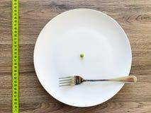 R?gime Souffrance de l'anorexie Pois cultivé d'image du plat blanc, avec la fourchette et la mesure photographie stock libre de droits