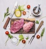 Rå grisköttbiff med grönsaker och örter, köttkniv och gaffel, på slut för bästa sikt för skärbrädaett trälantligt bakgrund upp Arkivfoto