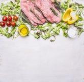 Rå grisköttbiff på trälantlig bakgrundsöverkant för tappningskärbrädagrönsallat, för körsbärsröda tomater, spansk peppar-, olja-  Arkivfoton