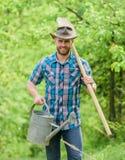 r Groeiende installaties De rijpe hoed van de kerelcowboy met gieter en schop Asdag Het planten van Bomen royalty-vrije stock foto's