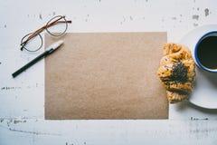 r Hoja en blanco del arte de la maqueta del papel, de la pluma, de los vidrios del ojo y de la taza de café vacíos de la mañana Fotografía de archivo libre de regalías