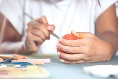 Ręka azjatykci dziecko dziewczyny rysunek i obraz na Easter jajku Fotografia Stock