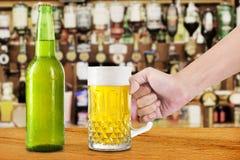 Ręka bierze piwo na stole Fotografia Stock