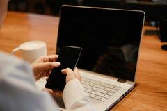 ręka biznesmena chwyta smartphone komputerowego laptop i cu Obraz Royalty Free