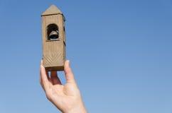 Ręka chwyta dzwonnicy miniatura na niebieskiego nieba tle Zdjęcie Stock