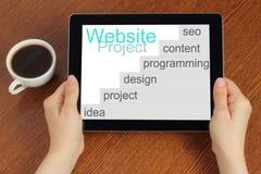 Ręka chwyta pastylki komputer osobisty z strona internetowa projekta rozwoju krokami Zdjęcia Royalty Free