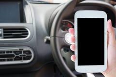 ręka chwyta telefon komórkowy z samochodem Fotografia Royalty Free