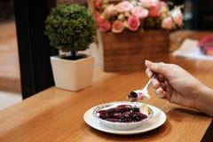Ręka na czarnej jagody cheesecake z sztucznego kwiatu bukietem na drewnianym stole Fotografia Stock