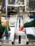Ręka pakuje zeszyty na linii produktowa Zdjęcia Stock