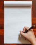 Ręka pisze na notatniku z piórem Zdjęcia Stock