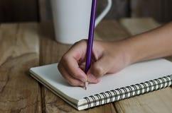 Ręka rysunek w otwartym notatniku na stole Obrazy Royalty Free