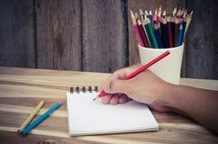Ręka rysunek w otwartym notatniku na stole Obrazy Stock