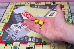 Ręka rzuca kostka do gry na tle kolorowe zamazane fantazj gry planszowa, hazardów momenty w dynamika Obrazy Royalty Free
