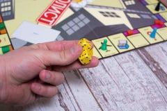 Ręka rzuca kostka do gry na tle kolorowe zamazane fantazj gry planszowa, hazardów momenty w dynamika Fotografia Stock