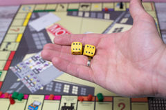Ręka rzuca kostka do gry na tle kolorowe zamazane fantazj gry planszowa, hazardów momenty w dynamika Obrazy Stock