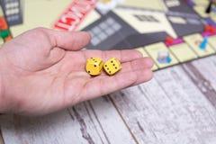 Ręka rzuca kostka do gry na tle kolorowe zamazane fantazj gry planszowa, hazardów momenty w dynamika Zdjęcie Royalty Free