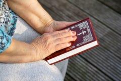 Ręka starsza kobieta na biblii Zdjęcie Stock