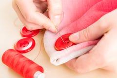 Ręka szwalny guzik na tkaninie Zdjęcie Royalty Free